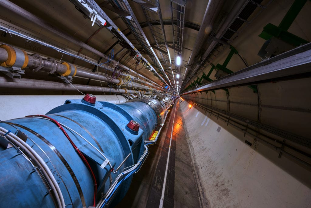A section of the 27 kilometer (16.6 mile) long circular track of Large Hadron Collider at CERN. Within the blue pipe, particles move at close to the speed of light. Image Credit: CERN